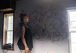 Artist Lorie Ranker paints a mural inside the Urban Art House. | Alex Rogals, Staff photographer