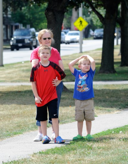 Cathy Woods of Forest park and Owen Bottorff , 7 and Connor Bottorff, 4 of Plainfield watch as the Roos is being demolished.