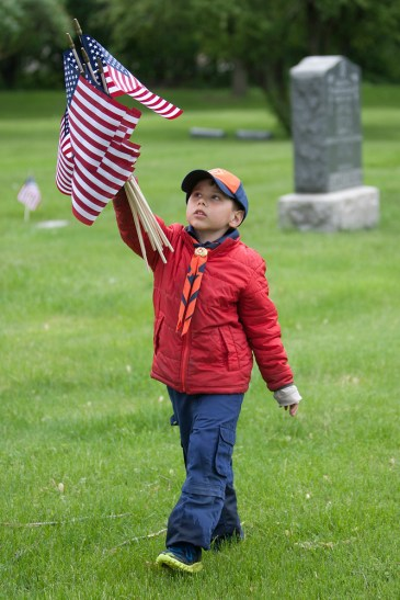 Tiger Cub Logan Wagner hoists American flags in the air while walking the grounds of Woodlawn Cemetery in Forest Park, Saturday, May 25, 2013. Logan and other scouts from the Des Plaines Valley Council planted more than 1,000 flags near markers where military veterans are buried.