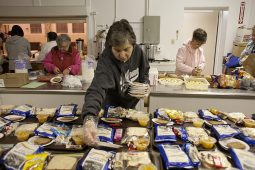 JoAnn Marra places plates of bread on food trays that will feed 48 men, women and children staying at a PADS shelter in St. John Lutheran Church in Forest Park Friday night. (David Pierini/staff photographer)