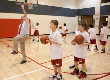 Thompson showing fifth- and sixth-grade players the mechanics of a layup. (David Pierini/staff photographer)