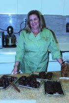 Owner and Chocolatier Donna stands next to her variety of bacon confections