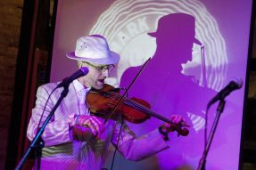 """Fred Lenoff tunes his violin at Chalk in Forest Park Saturday night as he prepares for a performance as """"Freddy Flow,"""" a self-styled hip hop artist from River Forest that refers to himself as the """"oldest living rapper in captivity (patent pending)."""" (File photo)"""