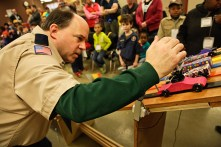 Forest Park scout leader John Bell readies five vehicles for a race at the Pack 109 Cub Scout Pinewood Derby at the Forest Park Community Center Saturday, Jan. 24. (Courtesy James Balodimas)