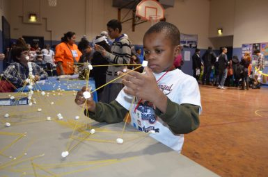 Omowunmi Adebajo, 6, a Betsy Ross Elementary School student, creates a structure using spaghetti and marshmallows. (Photo by Nick Samuel)