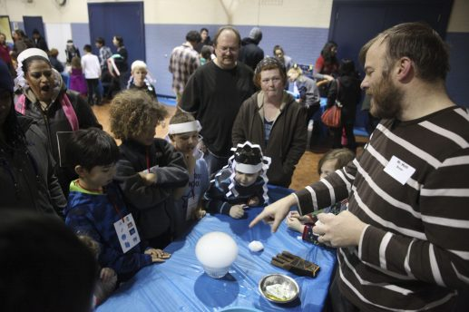 Kids and parents gather around to watch a dry ice experiment. (CHANDLER WEST/Staff Photographer)
