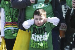 Vincent Niehus, 4, held his ears as emergency vehicles cruised down Madison Street during the Forest Park St. Patrick's Day Parade on Saturday. (CHANDLER WEST/Staff Photographer)