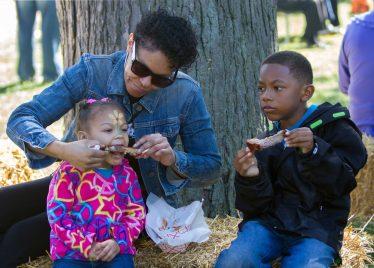 Tara Cowan feeds her granddaughter, Quinn Robinson, 2, a rib as grandson, Kaden Robinson, 7, looks on.   Jennifer T. Lacey/Contributor
