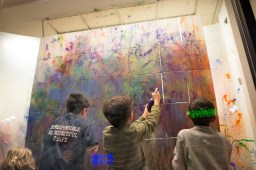 Children spray paint canvases in the window at Creativita. | Stacey Rupolo/Contributor
