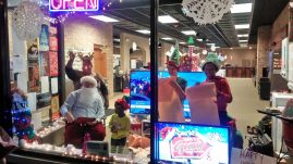 The Forest Park Review's Santa, (Dan Haley) and Rudolph (Jacquinete Baldwin) wave to shoppers in Santa's Grand workshop during their debut window display at Grand Appliances. | Courtesy Jacquinete Baldwin