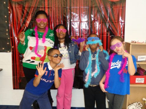 Mrs. Weaver (principal) with some students in the photo booth.