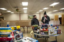 Matt Dowdle and Brian Powers look at toys donated to Forest Park. More than 160 boxes were put together along with food for needy children at the Forest Park Community Center. | William Camargo/Staff Photographer