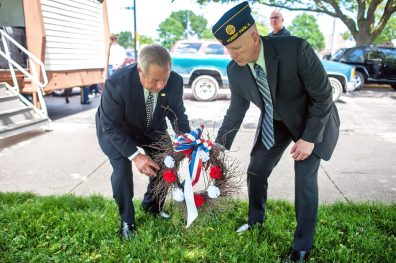 Forest Park Mayor Anthony Calderone and Sergeant Knute Weick take the memorial wreath to the landmark in The Park during the Memorial Day ceremony at The Park. | William Camargo/Staff Photographer