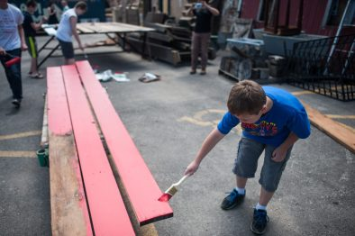 Donovan Wasilevich help paint the read stripes of the American flag at Re-Use Depot in Maywood, July 1. | William Camargo/Staff Photographer