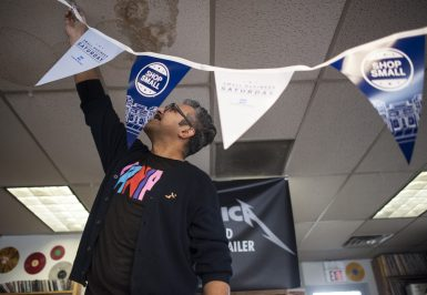 Edgar Baca puts up some decorations for Small Business Saturday at Old School Records in downtown Forest Park.   William Camargo/Staff Photographer