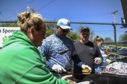 Tina Broton, Warren Riley and Lee Fitzgerald prepare cheeseburgers during the opening day BBQ. | William Camargo/Staff Photographer
