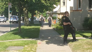 Police patrol the perimeter at the corner of Monroe Street and Kenilworth Avenue in Oak Park after the suspect crashed the stolen car and fled on foot down an alley. (Photo by Timothy Inklebarger| Staff)