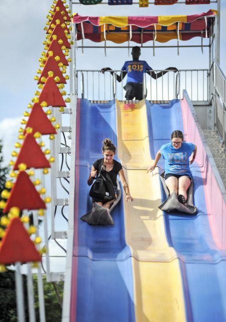 Lauren Justice and Sophia White race down a slide. | William Camargo/Staff Photographer