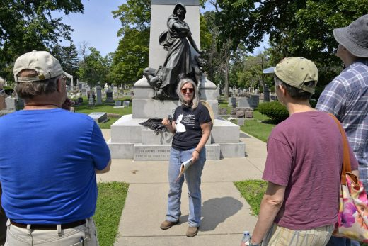 Amy Binns-Calvey, tour guide and board member of the Historical Society of Forest Park, discusses the monument with attendees on Saturday, Aug. 5, during a tour of the Haymarket Martyrs' monument and Radical Row at Forest Home Cemetery in Forest Park.   Alexa Rogals/Staff Photographer