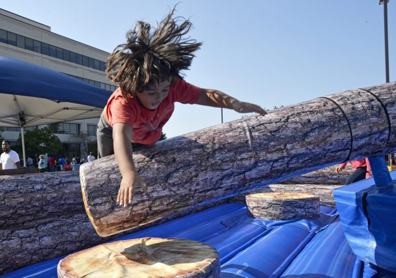 Venny Cordero, 7, of Chicago, tries to jump over a moving log during a game on Friday, Aug. 18, at the Proviso Back To School Bash at the D209 District Office in Forest Park. | Alexa Rogals/Staff Photographer