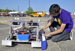 """Luis Solis, 17, a senior at Proviso Mathematics and Science Academy, takes the bumper off """"Monty"""" the robot. 