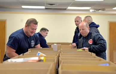 Firefighters organize and carry out boxes of non-perishable food to vehicles on Wednesday, Nov. 22, at the Howard Mohr Community Center on Jackson Boulevard in Forest Park. | Alexa Rogals/Staff Photographer