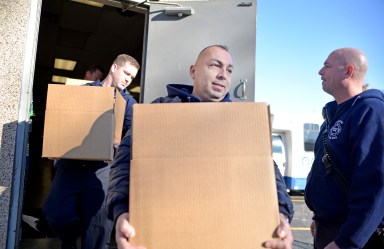 Firefighter Humberto Soto brings out boxes full of food. | Alexa Rogals/Staff Photographer