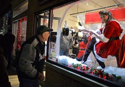 A passerby checks out the window display for Bliss Fashion Lounge during the annual Holiday Walk and Festival of Windows on Madison Street in downtown Forest Park on Dec.1. | Alexa Rogals/Staff Photographer