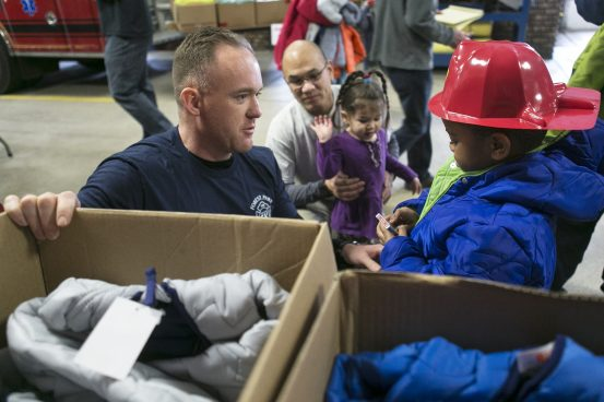 Travis Myers helps Avani Watson, 5, pick out a coat on Jan. 24, 2016 at the Forest Park Fire Department. | File photo