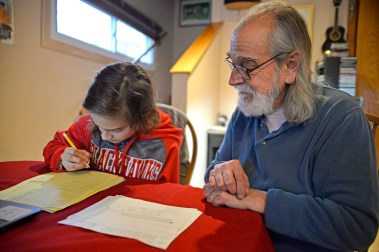 Seventh-grader Ernesto Gasse, left, gets tutored in algebra by his father, Daniel Gasse, after school on Friday, Dec. 15, at their home in Forest Park. | Alexa Rogals/Staff Photographer