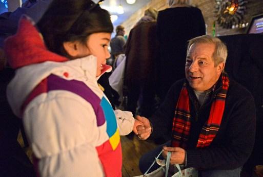 Ro Hriensaitong, 4, of Park Ridge, hands a wrapped gift to Mayor Anthony Calderone. | Alexa Rogals/Staff Photographer