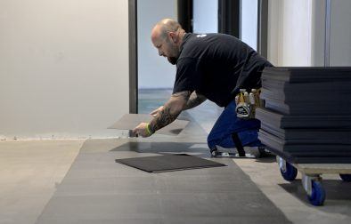 A construction worker puts in new vinyl flooring at the new Roos Recreation Center on Harrison Street. | Alexa Rogals/Staff Photographer