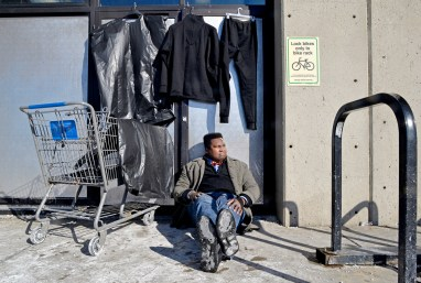 John Netherly sits for a photo along with the clothes he hands out outside of the Forest Park Blue Line L Station on Des Plaines Avenue in Forest Park. | Alexa Rogals/Staff Photographer