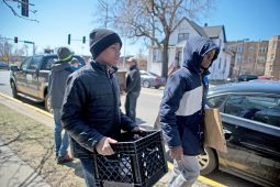 Kyle Cotton, 13, left, and Vincent Paxton, 13, carry tools and equipment to set up the mini food pantry on Saturday, April 7 in front of the Forest Park Public Library on Des Plaines Avenue. | Alexa Rogals/Staff Photographer
