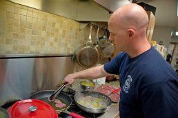 Firefighter Andrew Weber prepares dinner for the crew. | Alexa Rogals/Staff Photographer