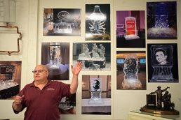 Jim Nadeau, owner of Nadeau's Ice House, points to a group of photos showing the work his business has done in the past. | Alexa Rogals/Staff Photographer