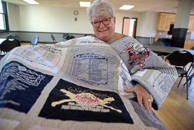 Sandy Byrnes shows off the quilt she made with every No Gloves Tournament T-shirt June 7, inside the Park District of Forest Park Administration Building on Harrison Street. | Alexa Rogals/Staff Photographer