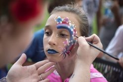 Mia Menendez, 11, of Forest Park, gets her face painted with patriotic colors by Brittany Thurma. | Alexa Rogals/Staff Photographer