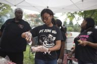 Meshiya Smith, from Pit Zone BBQ in Forest Park, squeezes their barbecue sauce on a pair of ribs. | Alexa Rogals/Staff Photographer