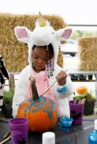 Kylee Taylor, 2, wears her unicorn costume as he paints a pumpkin.   Sarah Minor/Contributor