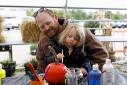 Greg Johnston, an employee of McAdam Landscaping Professionals, watches his daughter, Meara, 3, paint a pumpkin.   Sarah Minor/Contributor