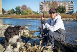 Dustin Murguia, with his dog, Lewis, near the Des Plaines River in Riverside. Murguia has placed first in four fishing tournaments over the last two years. | Alexa Rogals/Staff Photographer