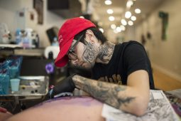 Luis Valdovinos, the shop owner, tattoos a client on at The Modern Electric tattoo studio on Madison Street in downtown Forest Park. | Alexa Rogals/Staff Photographer