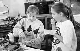 Anna Gillian and Christine Montes decorate Christmas cookies, and take a bite of the decorations.