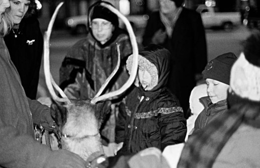 Children pose beside one of Santa's reindeer, a herd sponsored by Jerry Gleason Chevrolet/Geo and Dodge.