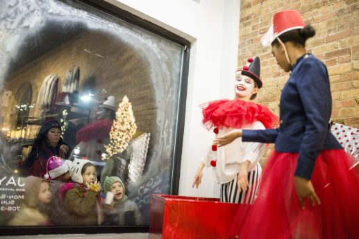 Lauren Militello, left, 14, of River Grove, and Hannah Brandon, 18, of Oak Park, perform in the live window display at Jayne as children look through the window and watch on Friday, Nov. 30, during the annual Holiday Walk in downtown Forest Park. | Alexa Rogals/Staff Photographer