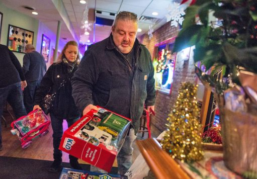 Kim Good, left, and Edward McCormick, both of Forest Park, bring in presents to donate to the pile under the tree during Mayor Calderone's Annual Community Toy Drive at R Place on Harlem Avenue in Forest Park. | Alexa Rogals/Staff Photographer