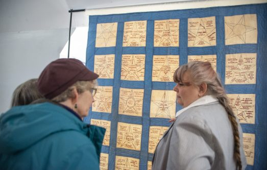 Attendees look over a community quilt displayed by the Historical Society for Forest Park on Saturday, March 23, 2019, during the first Community and History Festival at the Park District of Forest Park on Harrison Street. | ALEXA ROGALS/Staff Photographer