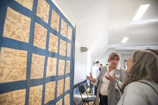 Volunteer Elizabeth Carpenter talks with attendees about the community quilt on Saturday, March 23, 2019, during the first Community and History Festival at the Park District of Forest Park on Harrison Street. | ALEXA ROGALS/Staff Photographer