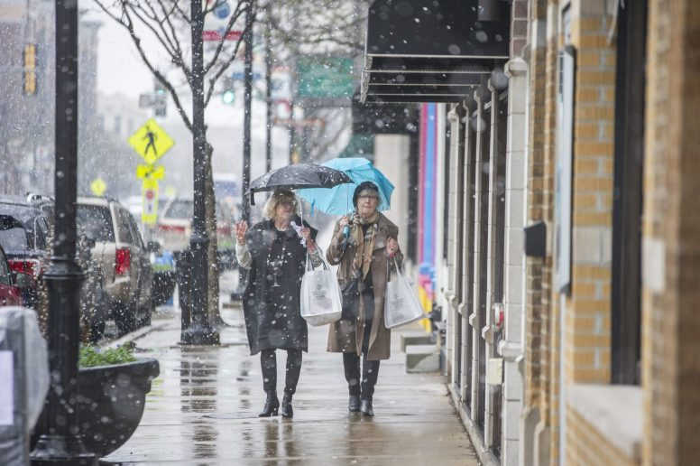 Attendees use umbrellas to shield the snow on April 27, during the annual Spring Wine Walk and Shop on Madison Street throughout downtown Forest Park. | ALEXA ROGALS/Staff Photographer